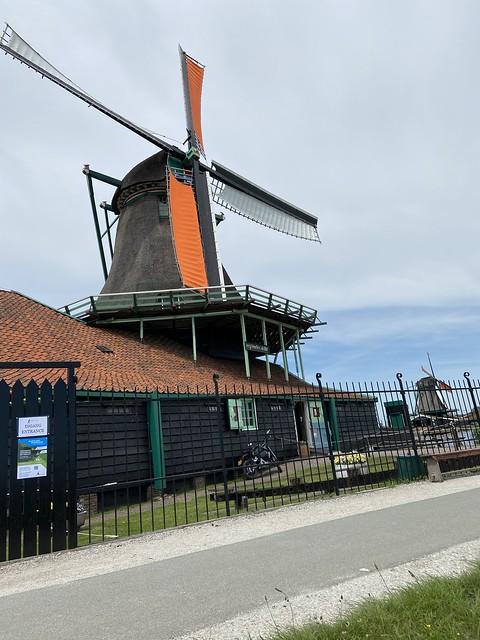 Zwarte Nederlandse molen met oranje wieken