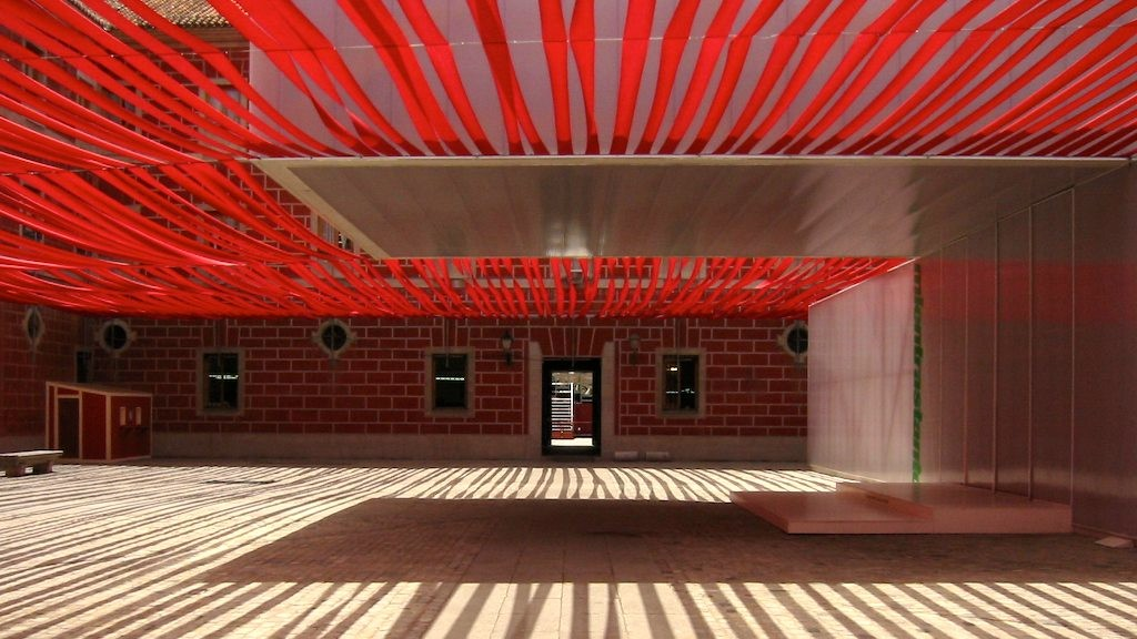 A courtyard with a canopy of red tape