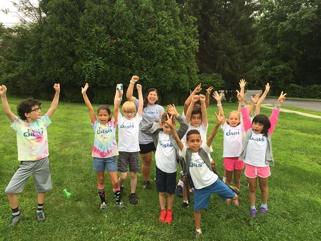 group of kids at camp with raised arms