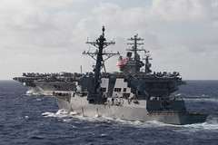 In this file photo, USS Ralph Johnson (DDG 114) steams in formation with USS Nimitz (CVN 68) during dual carrier operations with the Nimitz and Theodore Roosevelt Carrier Strike Groups in June.  (U.S. Navy/MC2 Logan C. Kellums)