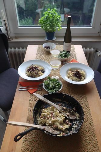 Bandnudeln mit Specksahnesoße und Pfifferlingen als Topping sowie Feldsalat als Beilage (Tischbild)