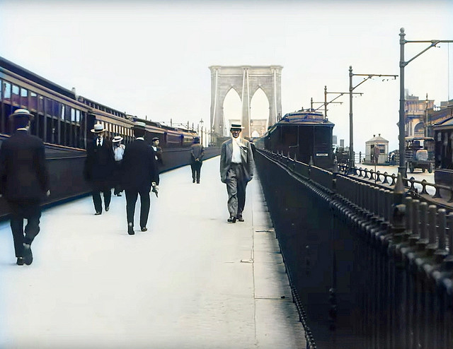 Just an average guy with a wind-blown tie and a straw hat crosses the Brooklyn Bridge to his job in Lower Manhattan. Trains zoom by and a Model T makes its way across the bridge in a hurry. New York. August 1911.