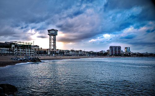 sea mar mare serene water waterfont beach shore coast seashore rock rocks city building tower architecture construction sky cielo cloud clouds sunset atardecer puestadelsol postadelsol shadow shadows tree palmtree color colors colores colour colours blue blu blau azul barcelona barceloneta labarceloneta outside outdoor