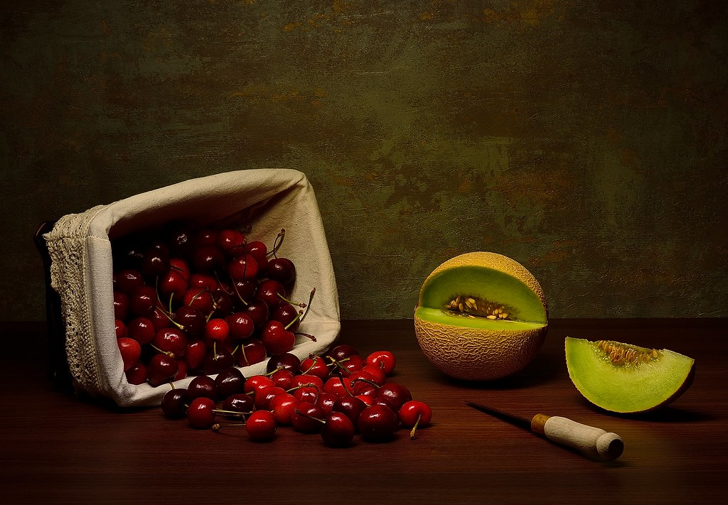 An overturned basket of cherries and melon