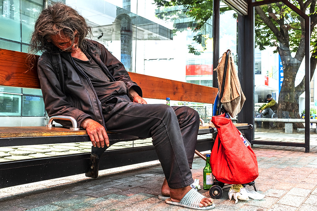 Homeless man sleeping at Nampo-dong bus stop on 7-5-20--Busan
