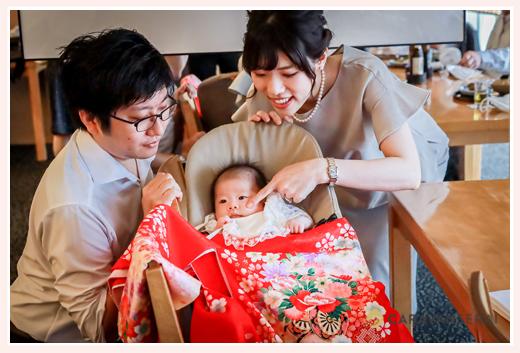 お宮参り後のお食事会 赤ちゃんをのぞき込むパパとママ