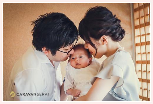 お宮参りの家族写真 赤ちゃんにキスをするパパとママ