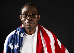 Personnel Specialist 1st Class Patrick Mbayoh, assigned to Strike Fighter Squadron (VFA) 137, poses for a photo with an American flag aboard USS Nimitz (CVN 68). (U.S. Navy/MC2 Greg Hall)