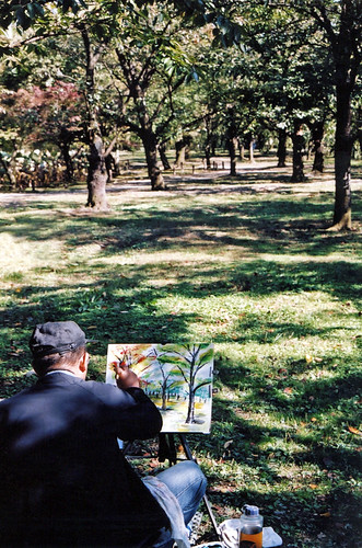 An artist painting trees in a park in Osaka, Japan