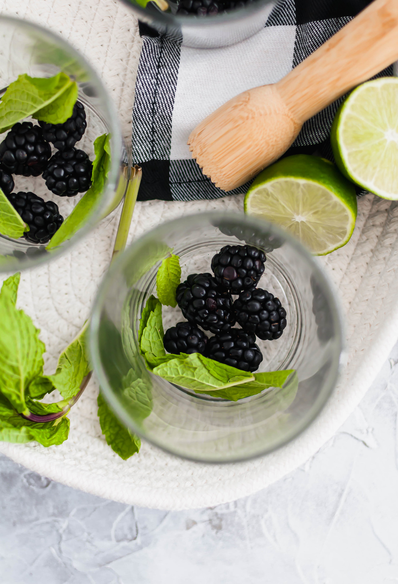 These Blackberry Mojitos will quickly become the drink of summer. An easy blackberry simple syrup and all the classic mojito ingredients are all you need for this refreshing cocktail. Ingredients for blackberry mojitos along with muddler.