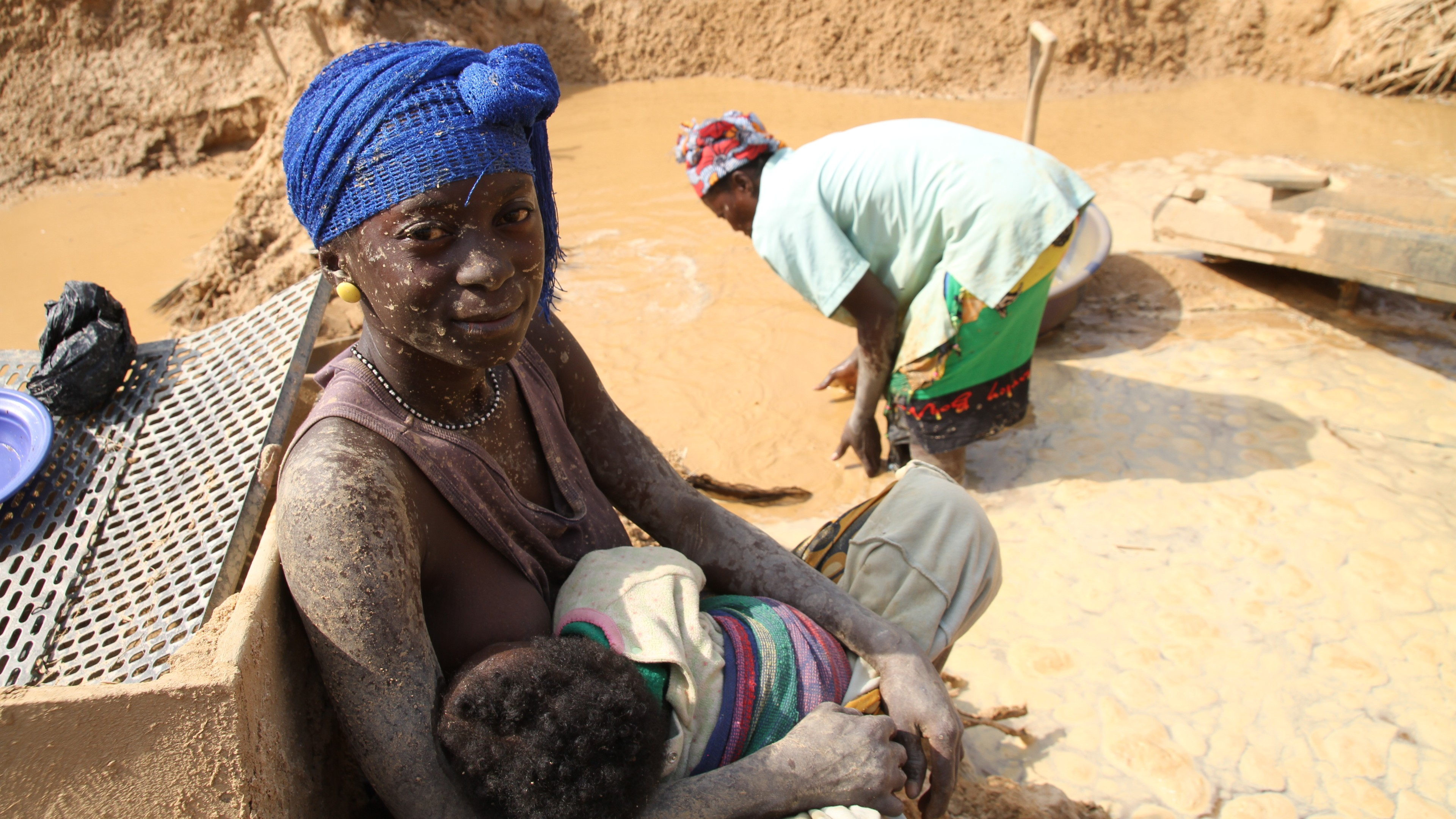A lady breastfeeds her baby while sitting in a clay mine