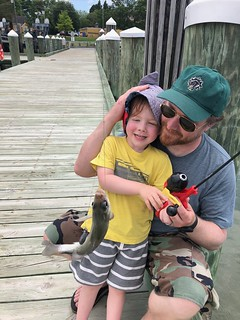 Photo of man and his young son holding a white perch