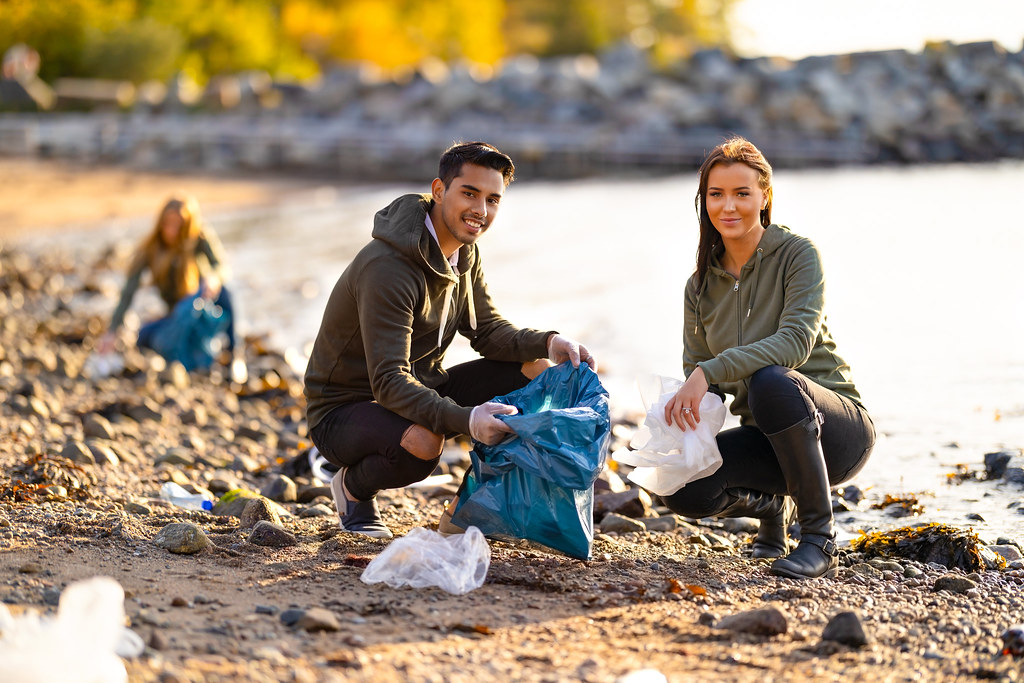 Male and female volunteer on beach picking up litter smiling