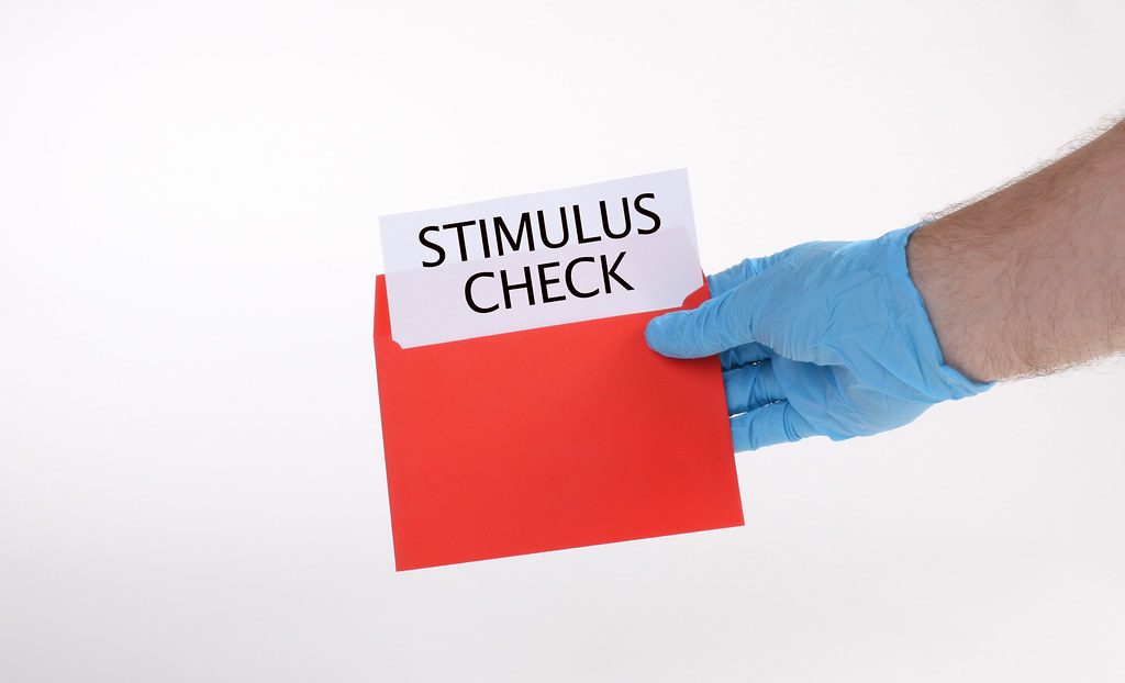Hand in medical gloves holds red envelope with stimulus ch… - Flickr