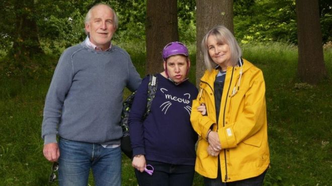 A woman with learning disabilities standing with her parents