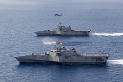 USS Gabrielle Giffords (LCS 10) and USS Montgomery (LCS 8) operate in the South China Sea, Jan. 28, accompanied by an MH-60S Sea Hawk from Helicopter Sea Combat Squadron (HSC) 23. (U.S. Navy/MC2 Chris Roys)
