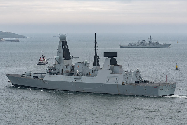HMS Defender (D36) in Plymouth Sound passing in front of HMS Northumberland (F238) at anchor