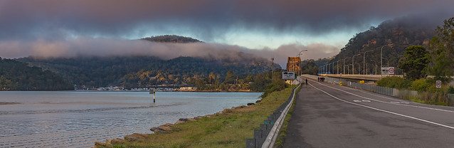 Panoramic misty morning by the river with bridge and road