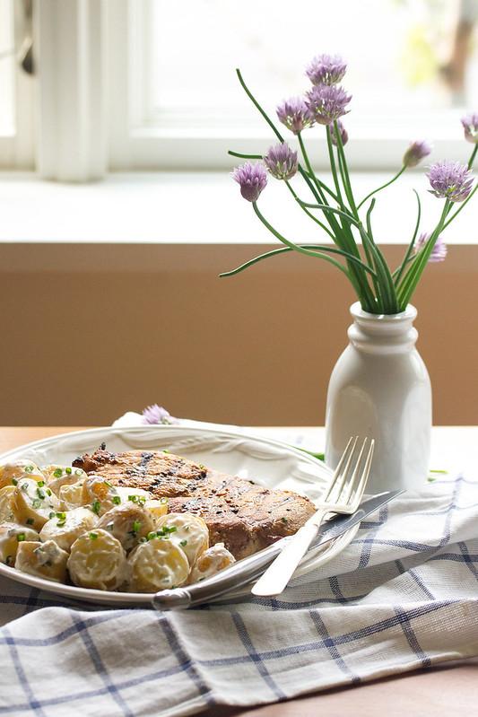 Yogurt-Chive Potato Salad on a Plate with a Pork Chop