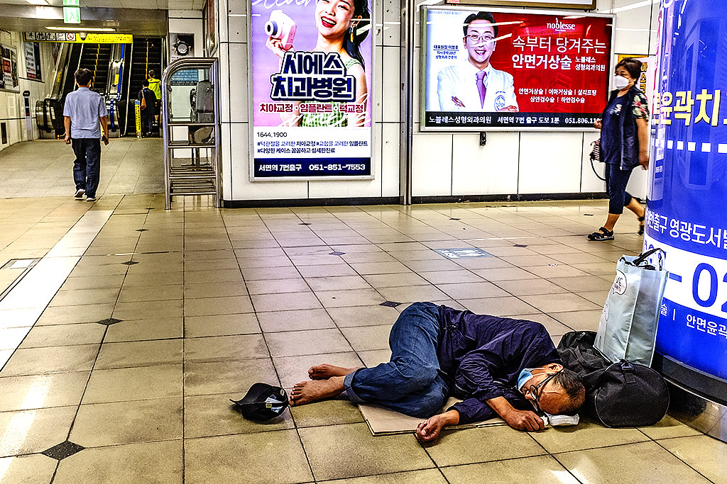 Homeless man sleeping on floor in underground concourse near Seomyeon Station on 7-12-20--Busan