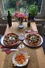 Pizzen mit Tomaten, Burrata und Basilikum (Tischbild)