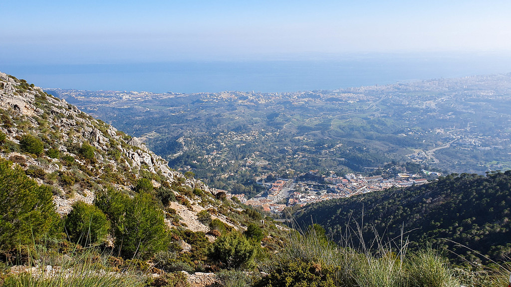 A side of the mountain in the left side of the photo, with the panorama of the village and the coast in the centre and the on the right.