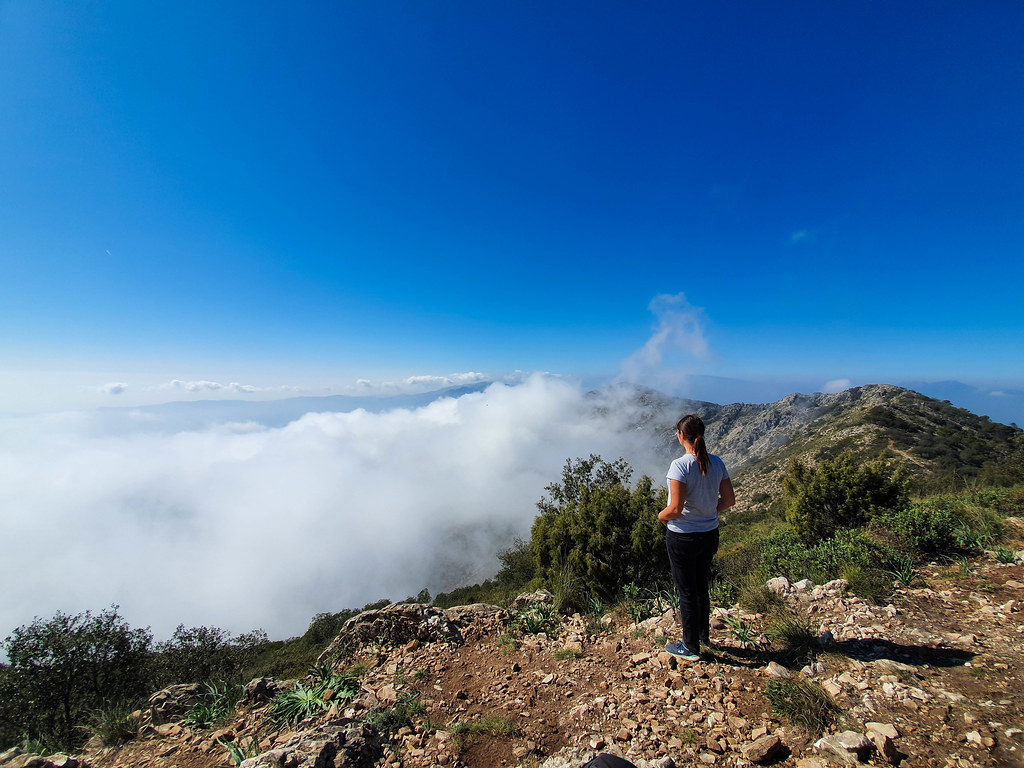I am standing in the right side of the photo, with my back at the camera, wearing a white tshirt, a black pair of jeans, with my hair in a pony tail, overlooking the scenery below. A cloud is raising from below, and the mountain peaks are peeking through it. Above, the sky is blue without any clouds.