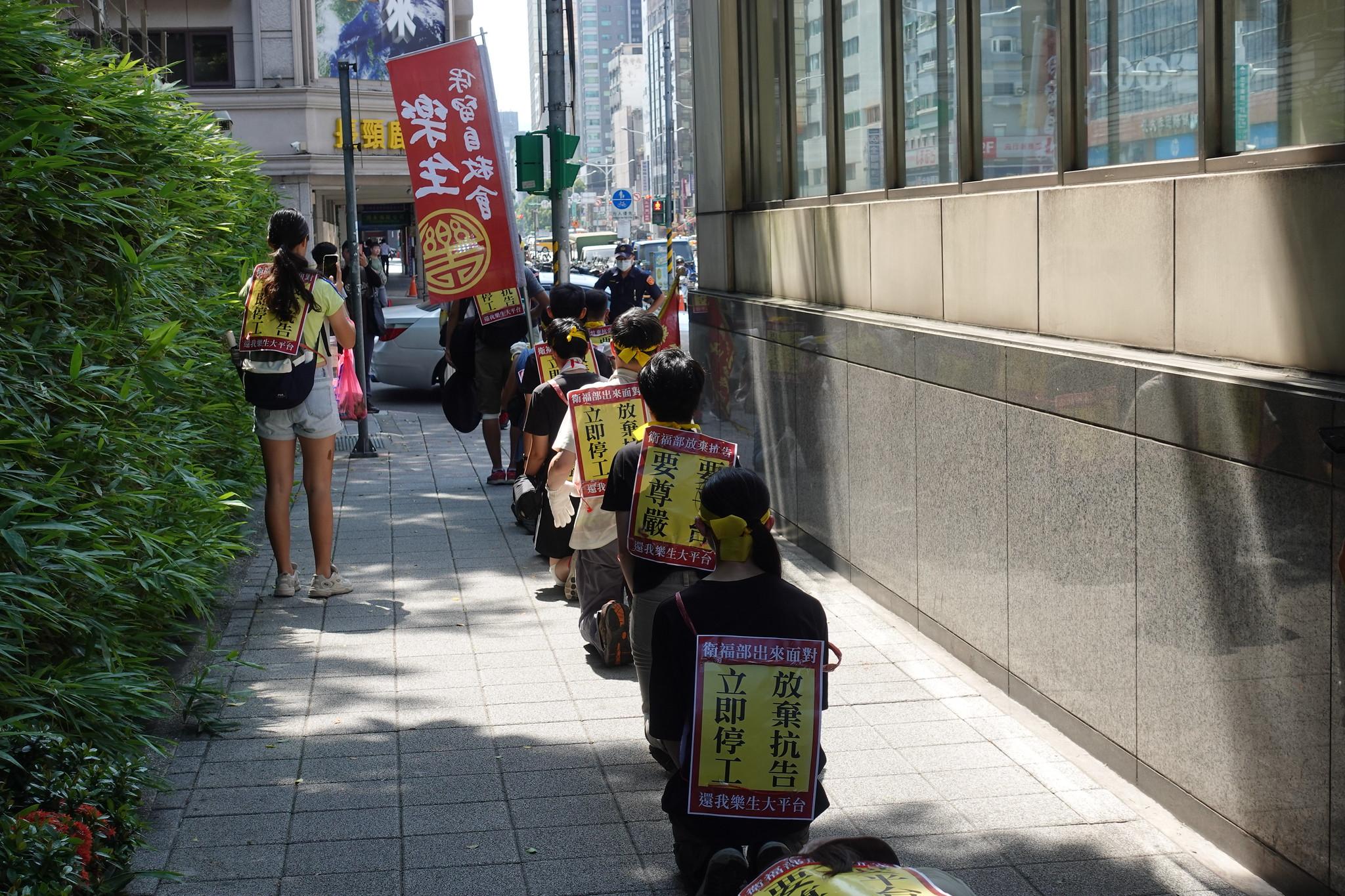 樂青在烈日下六步一跪苦行,從行政院出發前往衛福部。(攝影:張智琦)