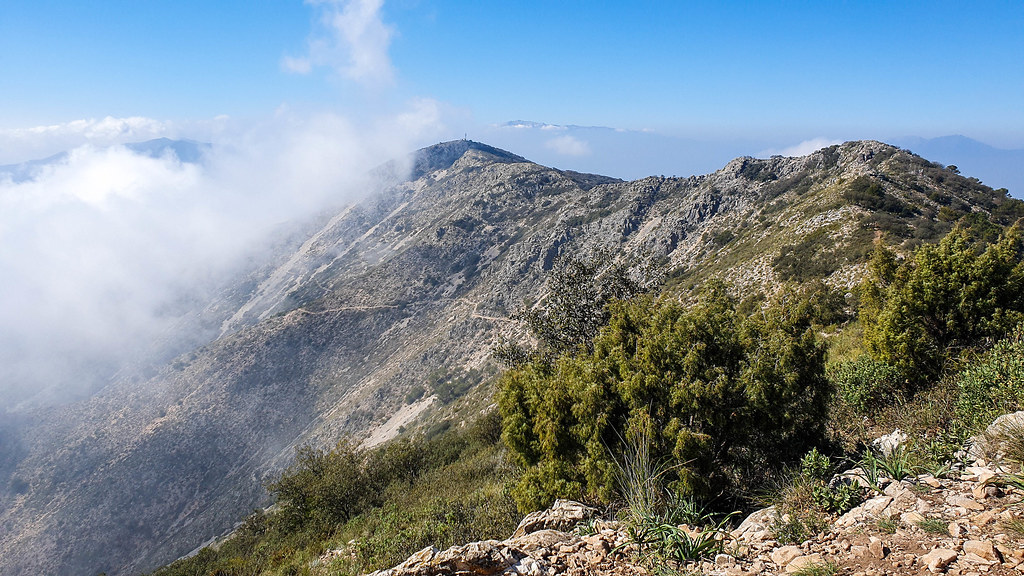 The view from the top towards the other peaks of Sierra de Mijas mountains, with a big white cloud coming in from the left side of the picture.