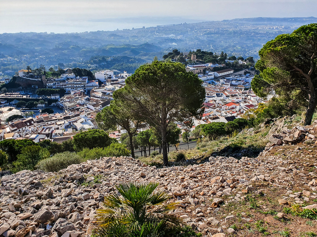 A view from the first part of the hike: in the front of the photo the terrain is covered in loose rocks, with a couple of green trees here and there. Below, in the centre of the photo, there is the panorama of the white village of Mijas Pueblo. On the top of the photo there is the blue sea.