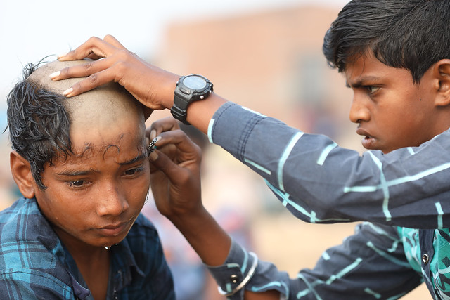 India, boy and hairdresser in Puri