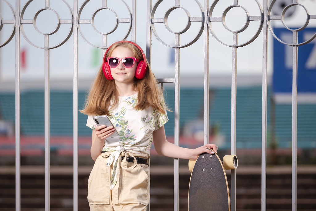 Teenager Lifestyle and Ideas. Portrait of Caucasian Teenage Girl Listening to Music in Wireless Headphones. Posing in Sunglasses With Longboard Outdoor.