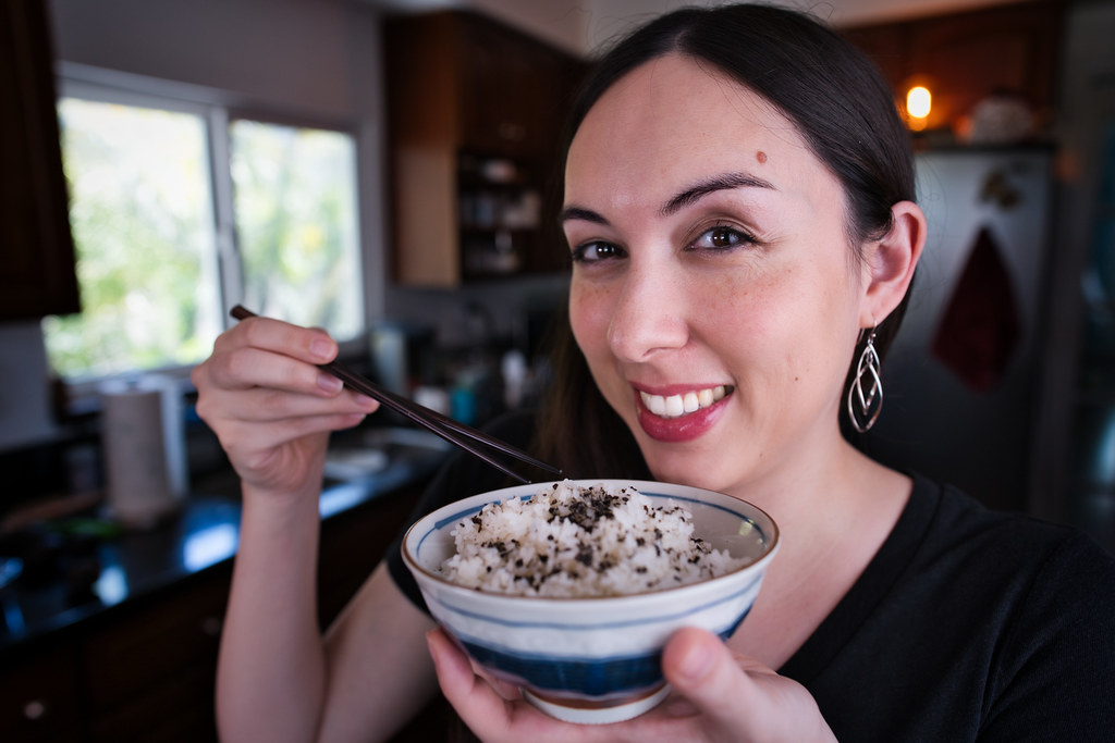 Allison holding a bowl of rice topped with furikake nori