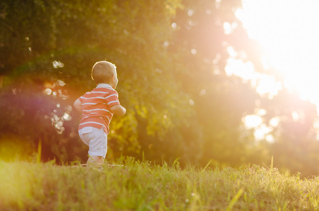 Young child is running around the sunny field