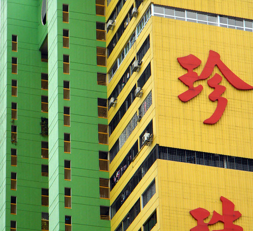 Singapore street with tall yellow and green buildings labelled with Chinese character