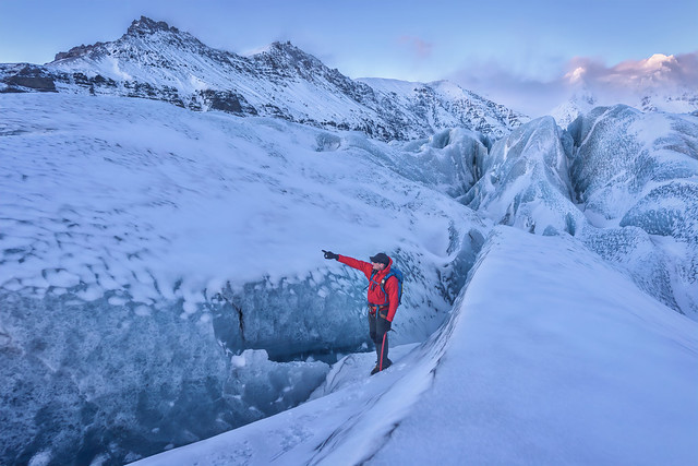 Trekking guide directing the way while hiking on a glacier at sunset, Vatnajokull (Glacier of Lakes) National Park, Iceland