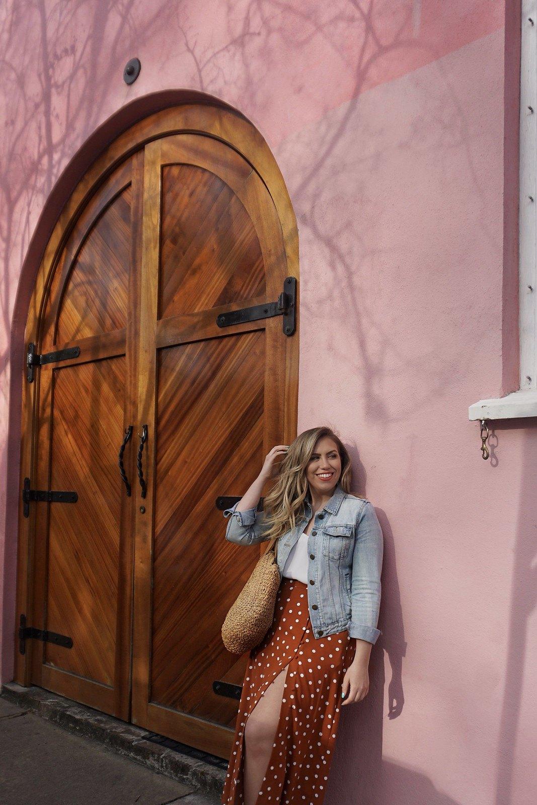 Charleston SC Pink Building | Spring Outfit Inspiration | Denim Jacket | Orange Polka Dot Skirt with Slit