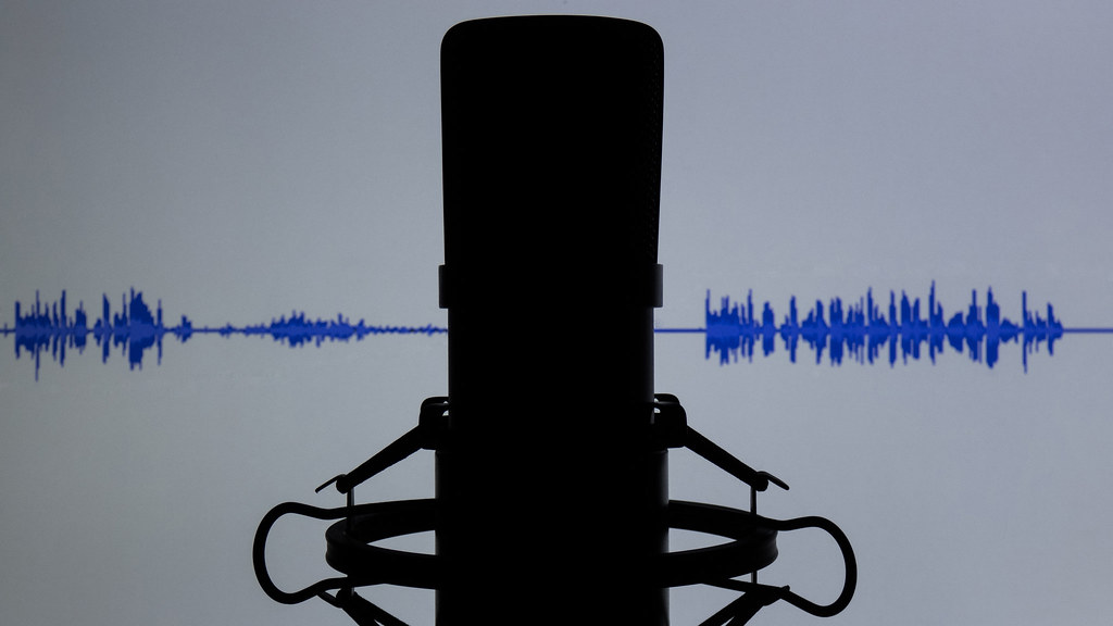 A black silhouette of a condenser microphone against a white background with a blue audio wave track spanning across the middle of the background.