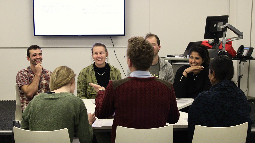 A group of researchers sitting around a table having a discussion