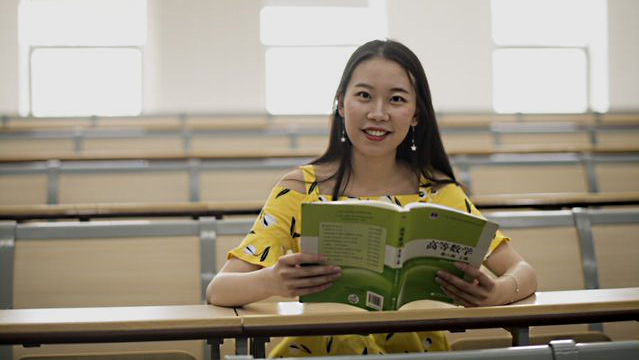 Photo of Li Nan (Beverly) holding a text book and looking at the camera.