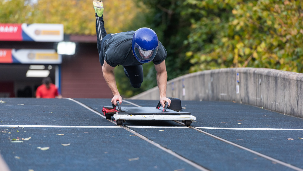 Skeleton athlete jumping onto a sled