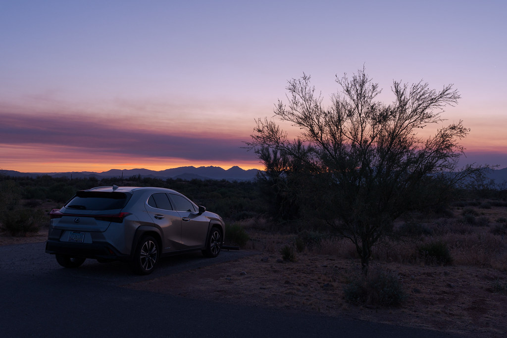 A view of my 2020 Lexus UX 250h parked next to a tree at the Fraesfield trailhead at sunrise in McDowell Sonoran Preserve in Scottsdale, Arizona in June 2020