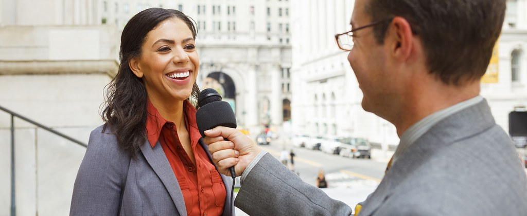 Woman outside of building being interviewed by journalist with a microphone