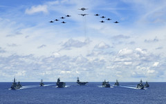 As aircraft from Carrier Air Wing 5 fly overhead, ships from the Ronald Reagan Carrier Strike Group, Royal Australian Navy and Japan Maritime Self-Defense Force steam in formation, July 21. (U.S. Navy/MC2 Codie L. Soule)