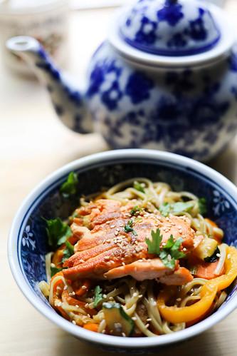 Paistettu rapea lohi jonka alla värikäs nuudeliannos josta näkyy erivärisiä vihanneksia. Taustalla sininen kannu jossa vihreää teetä