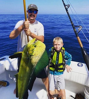 Photo of father and son holding large dolphin-fish