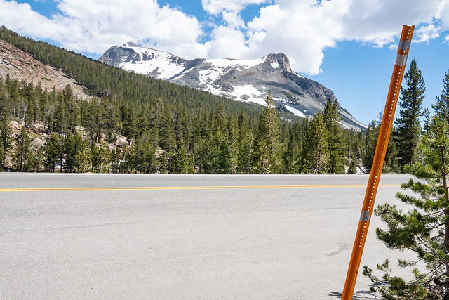 Close up of a snow marker stick (snowpole) along Tioga Pass, going through Yosemite National Park in California, showing snow removal crews the edge of the road and pavement