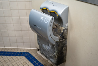 San Francisco, California - July 10, 2019: A very dirty, rotten and moldy Dyson Airblade hand dryer in a public restroom. The machine is broken | by m01229