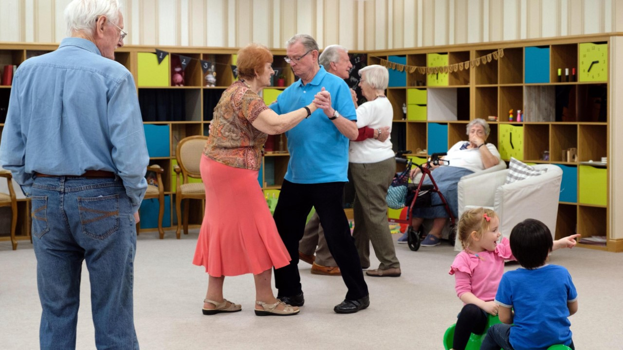 A group of people of mixed ages dancing and playing