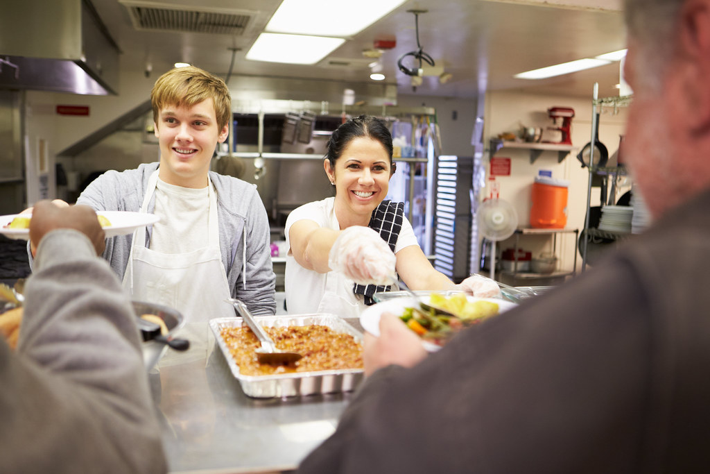 Two young volunteers serving food as part of their placement
